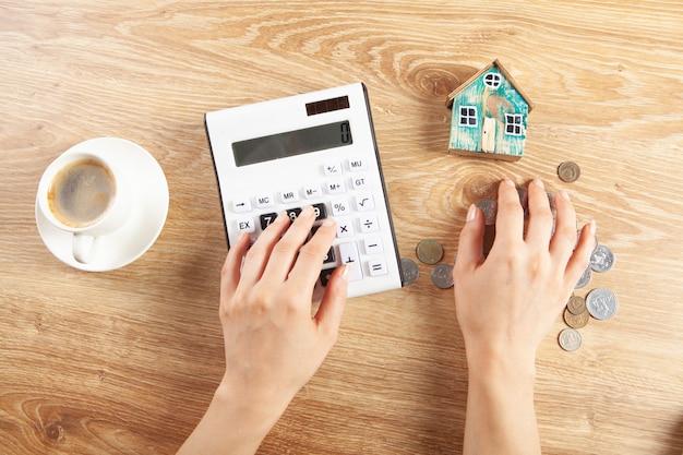 Kobieta oblicza wydatki w domu na kalkulatorze
