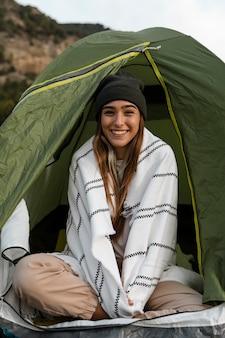 Kobieta obozująca i siedząca w namiocie