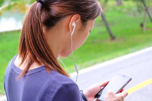 Kobieta obserwująca ją w smartfonie do wyboru muzyki przed ćwiczeniami.