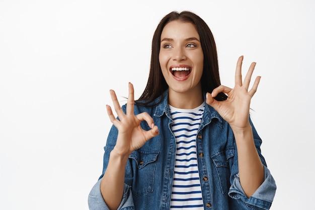 Kobieta ocenia coś fajnego, polecającego, zadowolonego patrzącego na sprzedaż i uśmiechającego się, upewniać się, że ok, zero gestu, kiwać głową z aprobatą, stać na białym