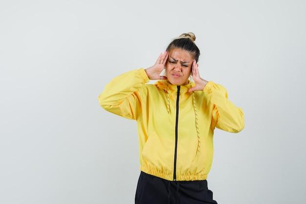Kobieta ociera skronie w sportowym garniturze i wygląda na zmęczoną. przedni widok.