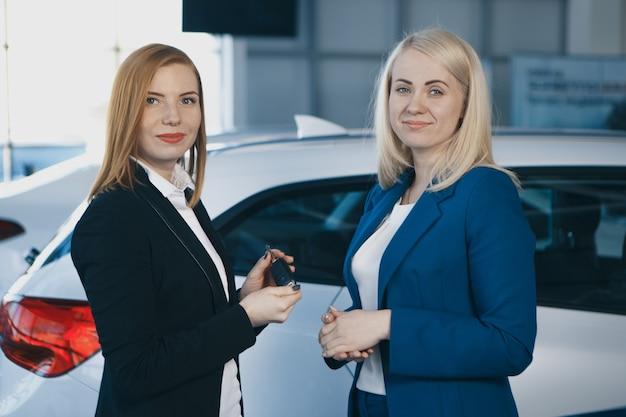 Kobieta odbiera kluczyki do samochodu od dealera