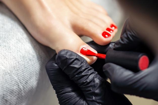 Kobieta odbiera lakier do paznokci z czerwonym lakierem do paznokci na stopy.