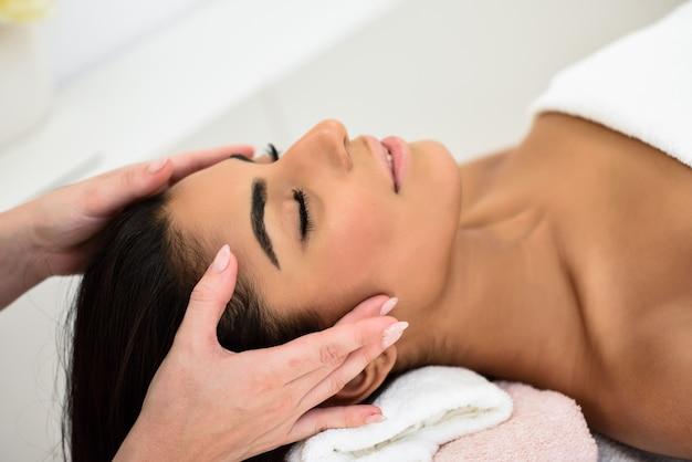Kobieta odbiera masaż głowy w centrum odnowy biologicznej spa.