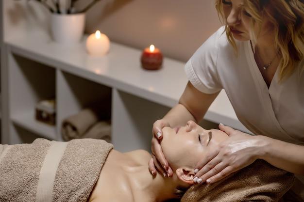 Kobieta odbiera masaż głowy w salonie spa, widok z boku.