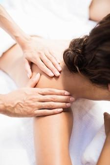 Kobieta odbiera masaż pleców od masażysty w spa