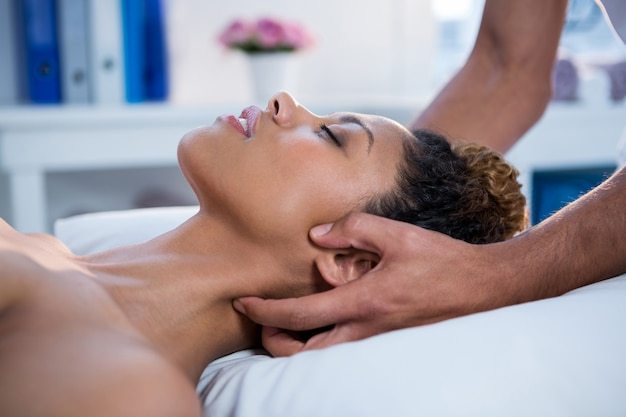 Kobieta odbiera masaż szyi od fizjoterapeuty