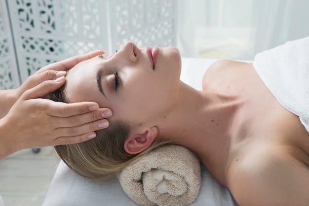 Kobieta odbiera masaż twarzy w spa
