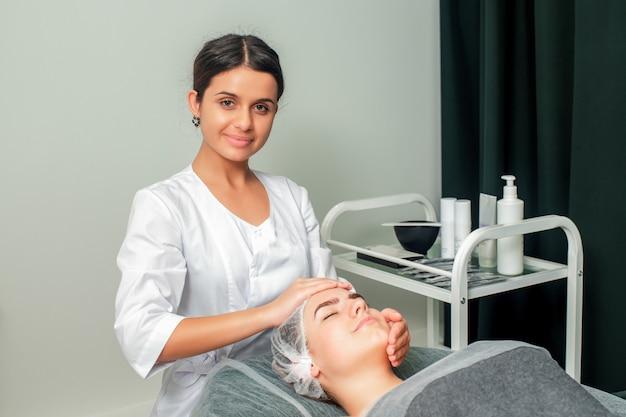 Kobieta odbiera masaż twarzy.