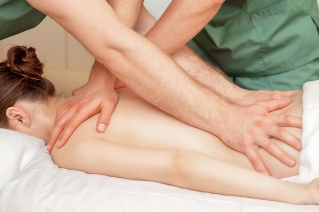 Kobieta odbiera masaż w czterech rękach.