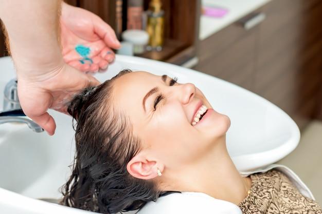 Kobieta odbiera mycie włosów.