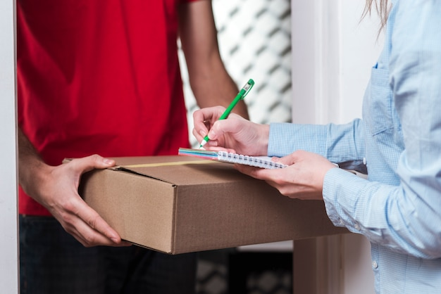 Kobieta odbiera paczkę od kuriera i podpisuje formularz z bliska