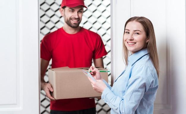 Kobieta odbiera paczkę od kuriera i podpisuje formularze