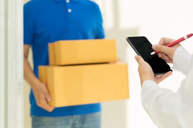 Kobieta odbiera pakiet i podpisanie na cyfrowy telefon komórkowy od człowieka dostawy