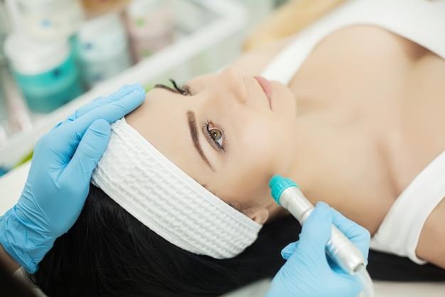 Kobieta odbiera profesjonalny peeling pędzlem w gabinecie kosmetologii