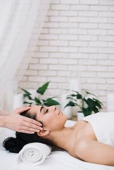 Kobieta odbiera relaksujący masaż twarzy