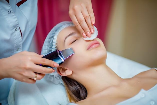 Kobieta odbiera ultradźwiękowy złuszczanie twarzy przy kosmetologia salonem.