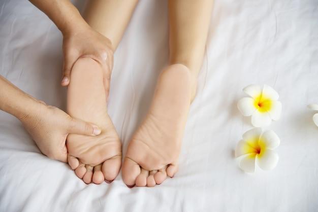 Kobieta odbiera usługi masażu stóp z masażystka bliska pod ręką i stóp - zrelaksować się w koncepcji usługi terapii masażu stóp