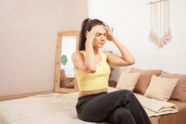 Kobieta odczuwa ból głowy, silny dyskomfort podczas uprawiania sportu.