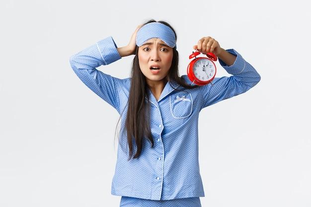 Kobieta odczuwająca panikę jako alarm, spóźniająca się do pracy, zaspana na poranny egzamin, trzymająca rękę na głowie i marszcząca brwi zdenerwowana, stojąca w niebieskiej piżamie i masce do spania z niepokojem