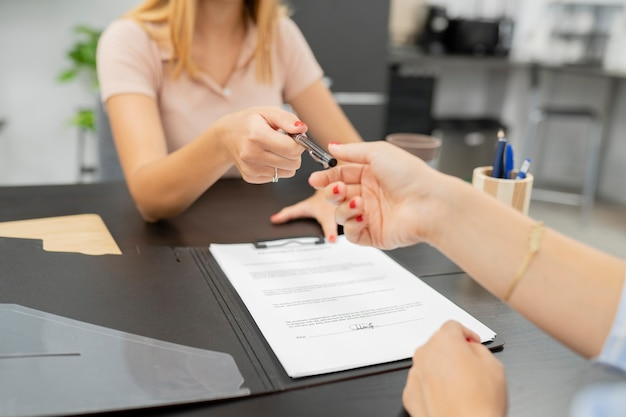 Kobieta oddająca długopis, aby podpisać umowę
