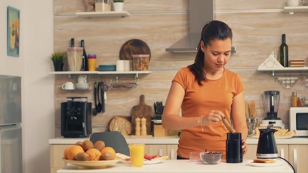 Kobieta oddanie ziaren kawy w młynku rano. gospodyni w domu robi świeżo mieloną kawę w kuchni na śniadanie, pije, miele kawę espresso przed pójściem do pracy