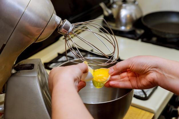 Kobieta oddziela białka od żółtka w misce miksera