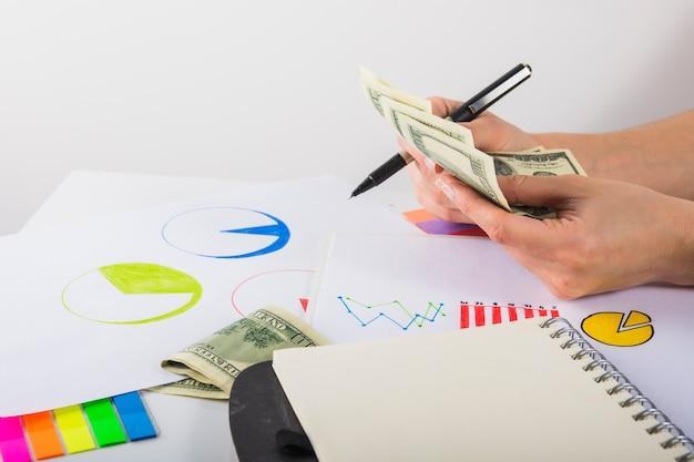 Kobieta odliczający pieniądze przy stołem
