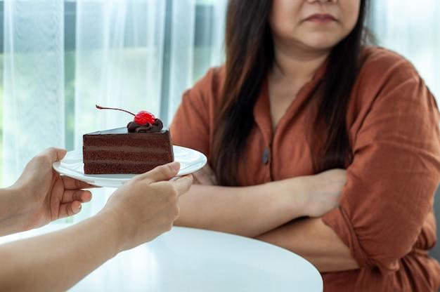 Kobieta odmawia jedzenia ciasta czekoladowego
