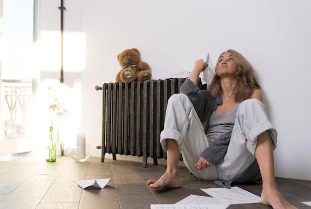 Kobieta odpala papierowy samolot siedząc na podłodze w swoim mieszkaniu