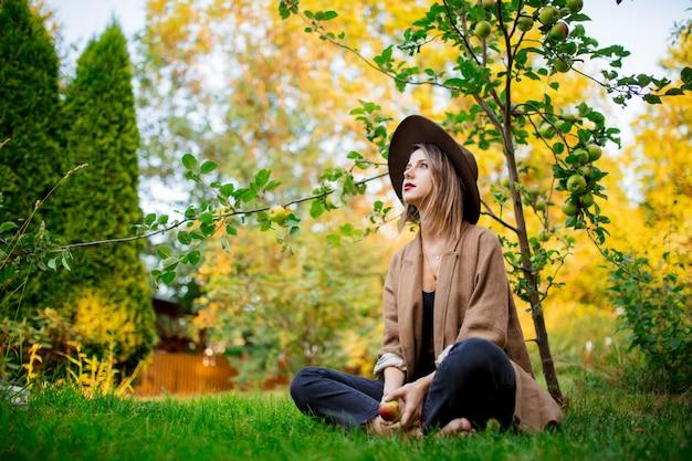 Kobieta odpocząć w ogrodzie w pobliżu młodej jabłoni