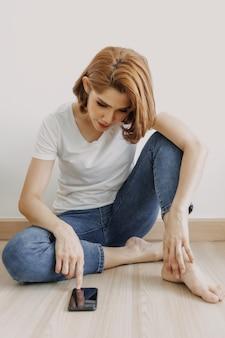 Kobieta odpoczywa i relaksuje się w pokoju ze smartfonem w dłoni