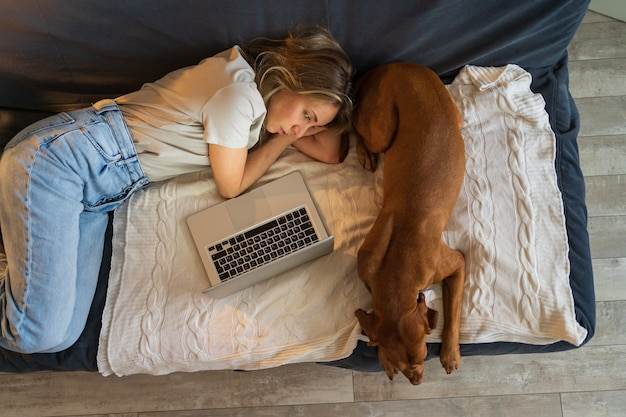 Kobieta odpoczywa leżąc na kanapie, pracując na laptopie z pięknym psem wyżeł węgierski krótkowłosy w domu widok z góry. leniwa rozrywka