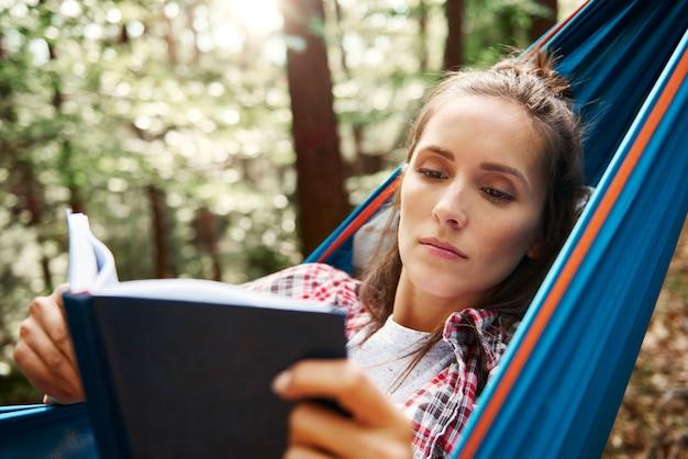 Kobieta odpoczywa na hamaku i czyta książkę