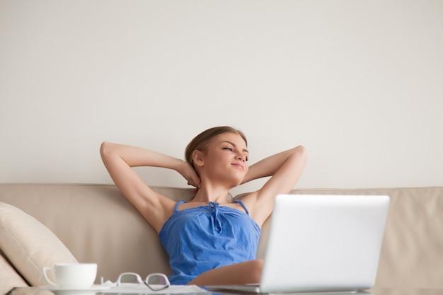 Kobieta odpoczywa na kanapie w domu po pracy robić