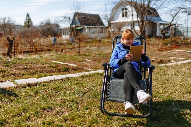 Kobieta odpoczywa na krześle z tabletem w swojej daczy