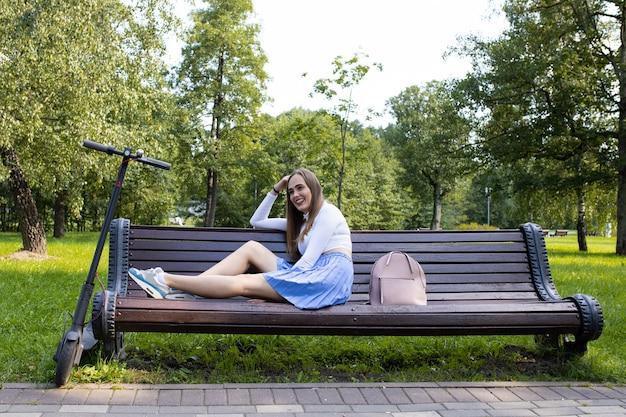 Kobieta odpoczywa na ławce w parku po wycieczce na skuter elektryczny