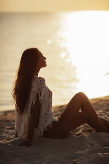 Kobieta odpoczywa na plaży podczas wakacji