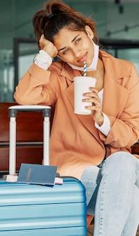 Kobieta odpoczywa na swoim bagażu na lotnisku i pije kawę podczas pandemii