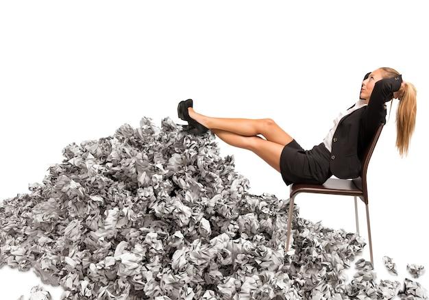 Kobieta odpoczywa, opierając się na stosie papieru