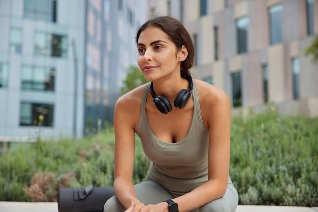 Kobieta odpoczywa po dobrym treningu fitness ubrana w strój sportowy siedzi na świeżym powietrzu i skupiona na dystansie myśli o planowaniu myśli jak poprawić zdrowie ciężko pracuje nad utrzymaniem formy
