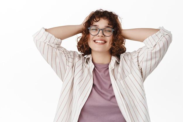 Kobieta odpoczywa, trzyma ręce za głową i wygląda na zadowoloną, ciesząc się weekendem, stojąc na białym tle.