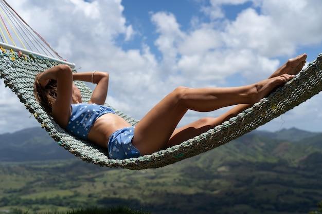 Kobieta odpoczywa w hamaku na zewnątrz widok na góry wakacje i koncepcja podróży