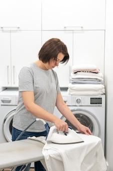 Kobieta odprasowywa białą koszula na pokładzie w pralni pokoju z pralką