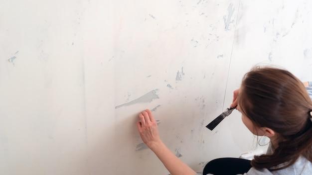Kobieta odrywa tapetę