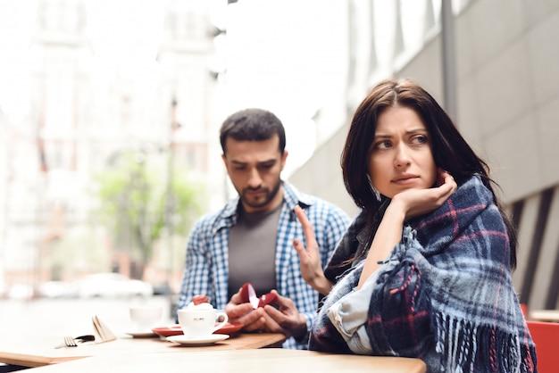 Kobieta odrzuca propozycję małżeństwa na tarasie kawiarni.