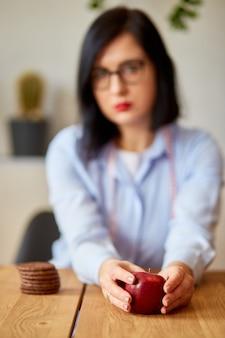 Kobieta odrzucająca niezdrową żywność lub niezdrową żywność, taką jak ciastka lub deser, i wybierając zdrową żywność