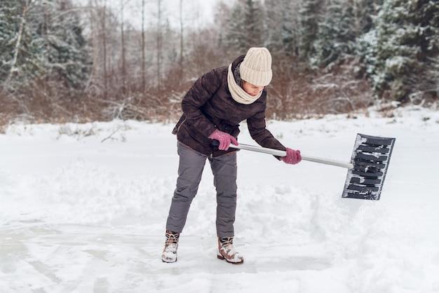 Kobieta odśnieżająca łopatą w zimie.