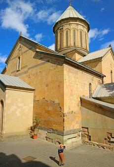 Kobieta odwiedzająca przed katedrą tbilisi sioni