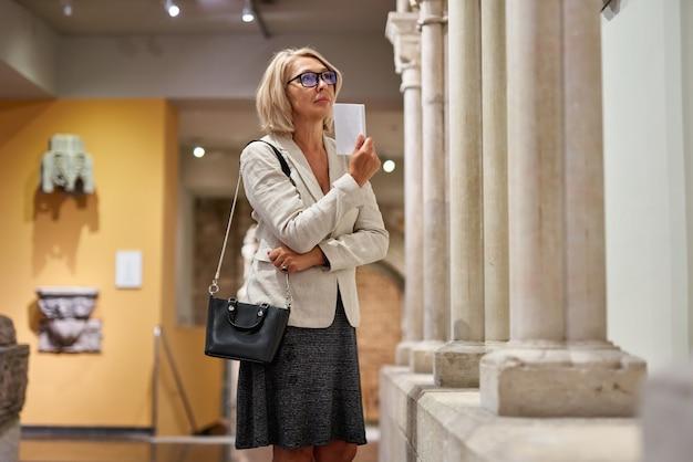 Kobieta odwiedzająca w pobliżu kolumn w muzeum historycznym, trzymająca broszurę z programem wystawienniczym